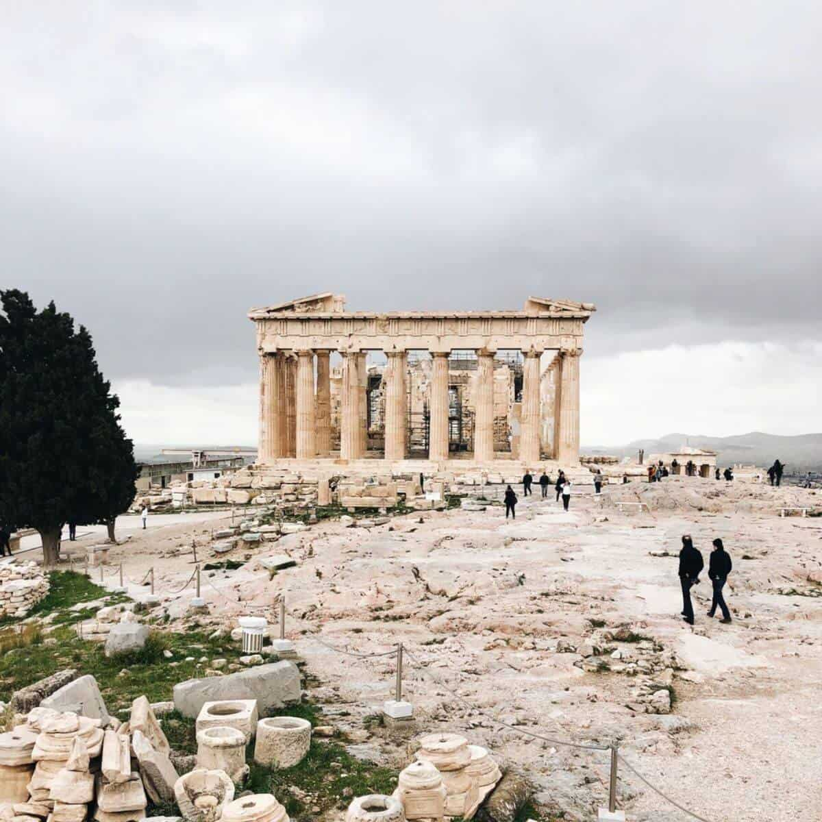 People walking towards Acropolis of Athens in Greece on a cloudy day.