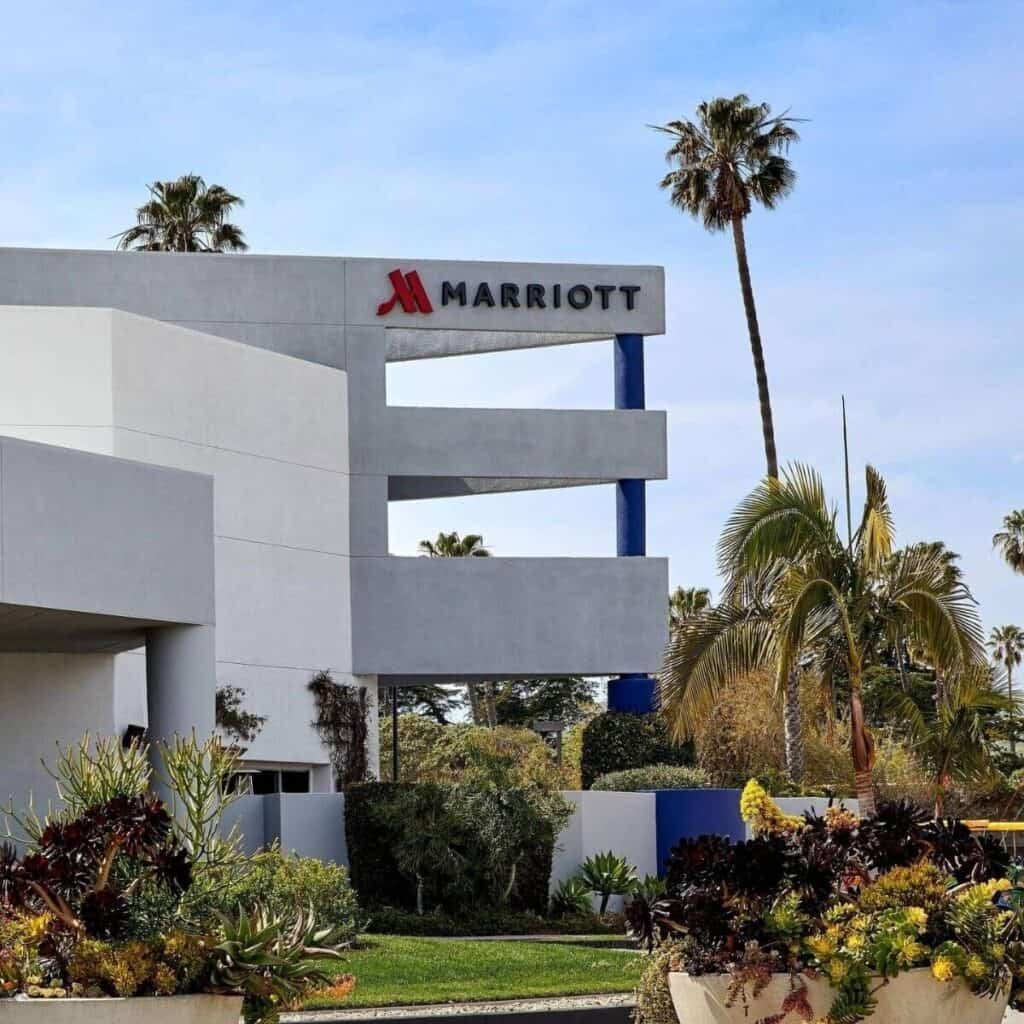 Exterior of a Marriott hotel with palm trees surrounding it.