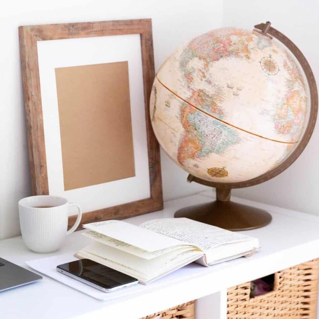 Globe, notebook, phone, mug, and frame on a table.