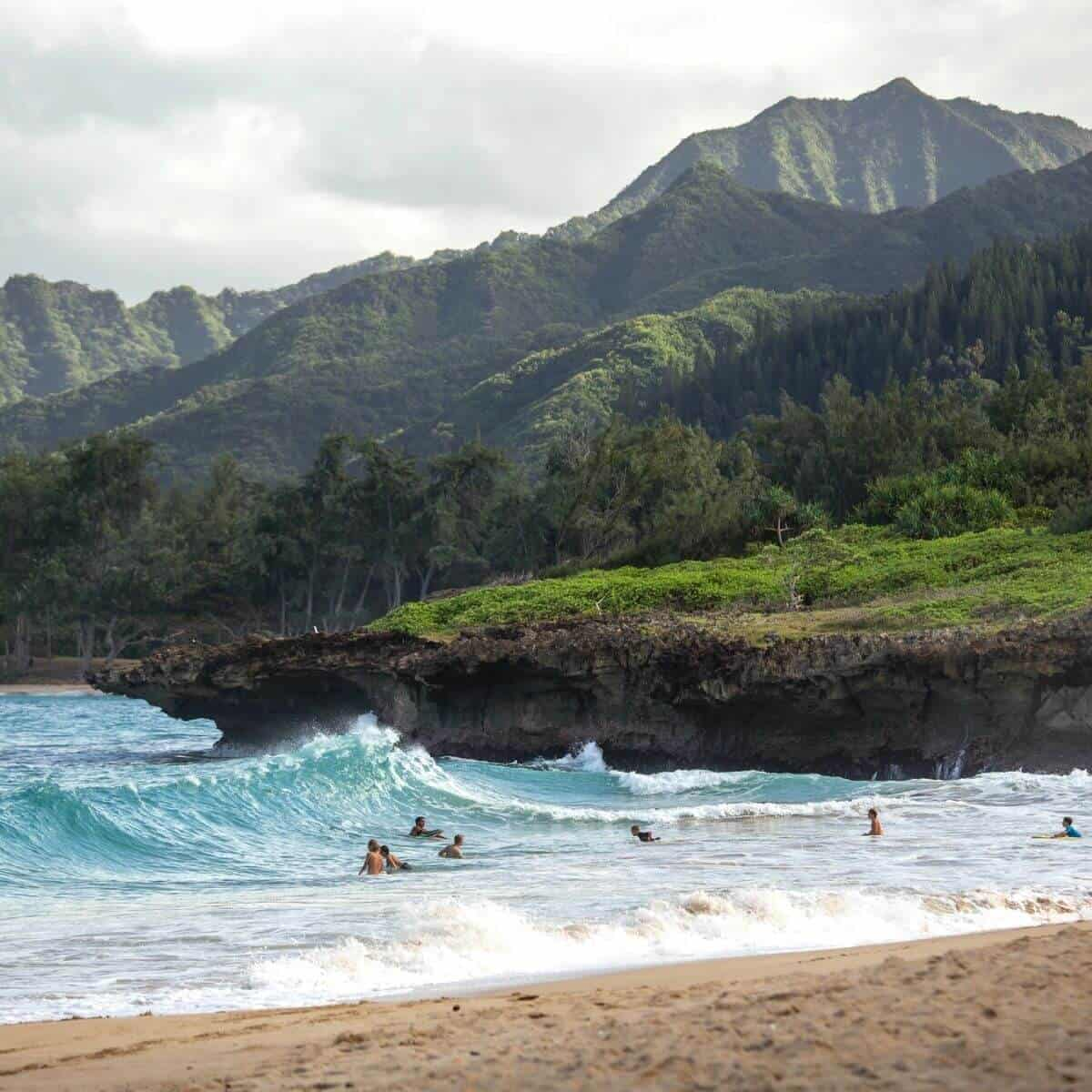 People swimming at a beach in Hawaii with mountains in the background.