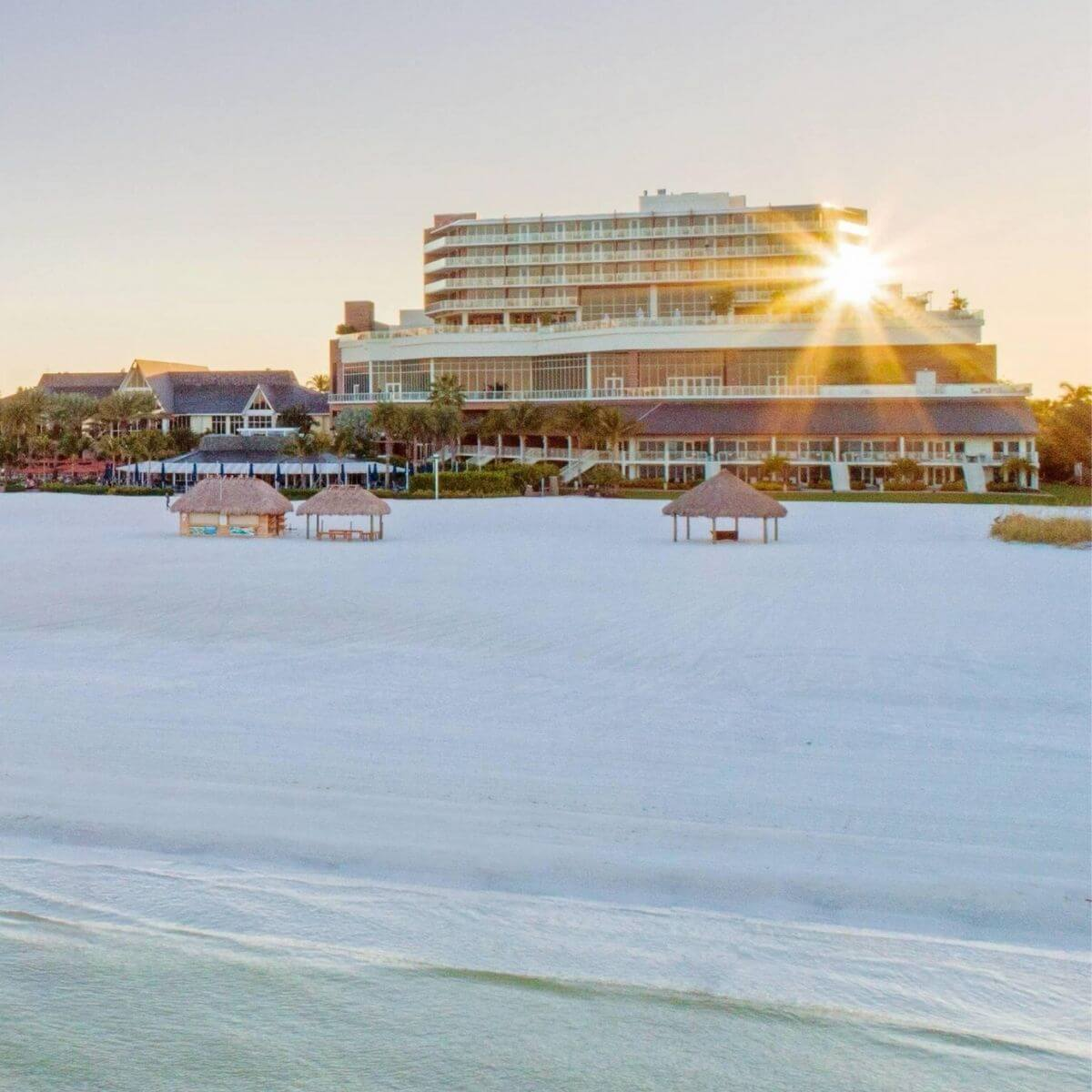 View of JW Marriott Marco Island Beach Resort from the ocean with the sun behind it.