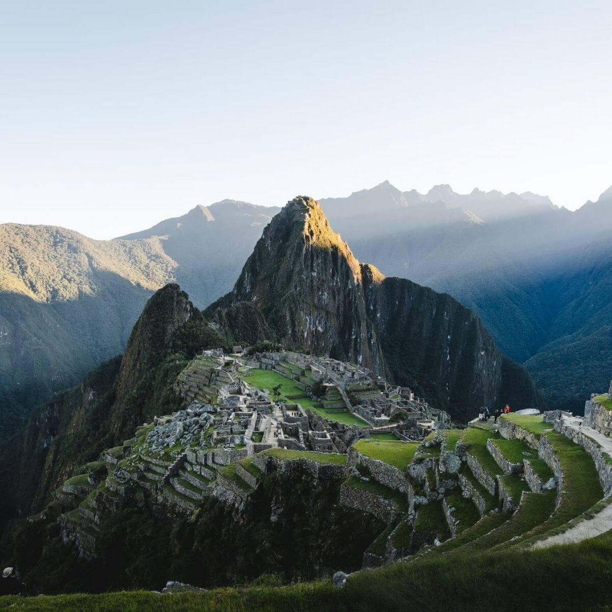 Machu Picchu with light rays shining behind it.