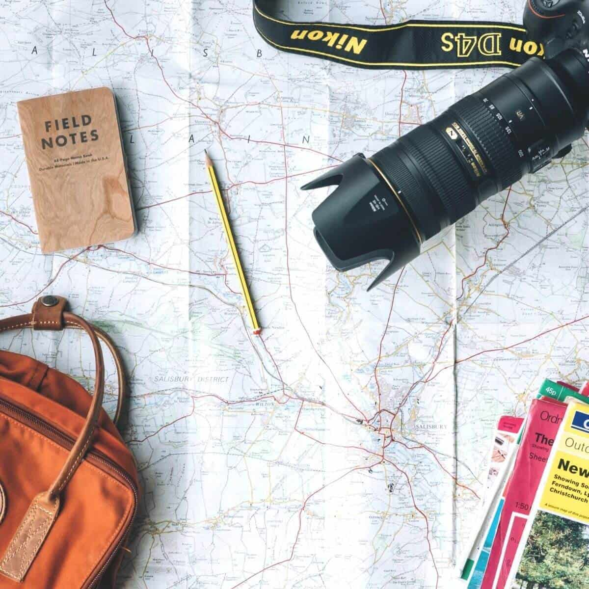 Camera, notebook, backpack, and books on top of a map.