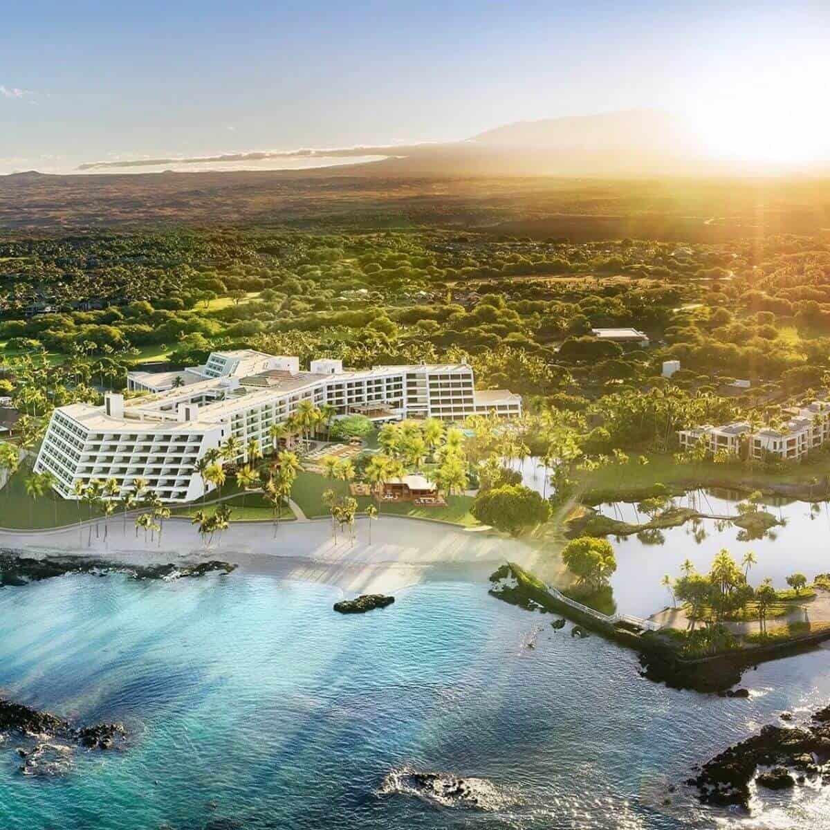 Aerial view of Mauna Lani Resort, the water, and trees behind it.