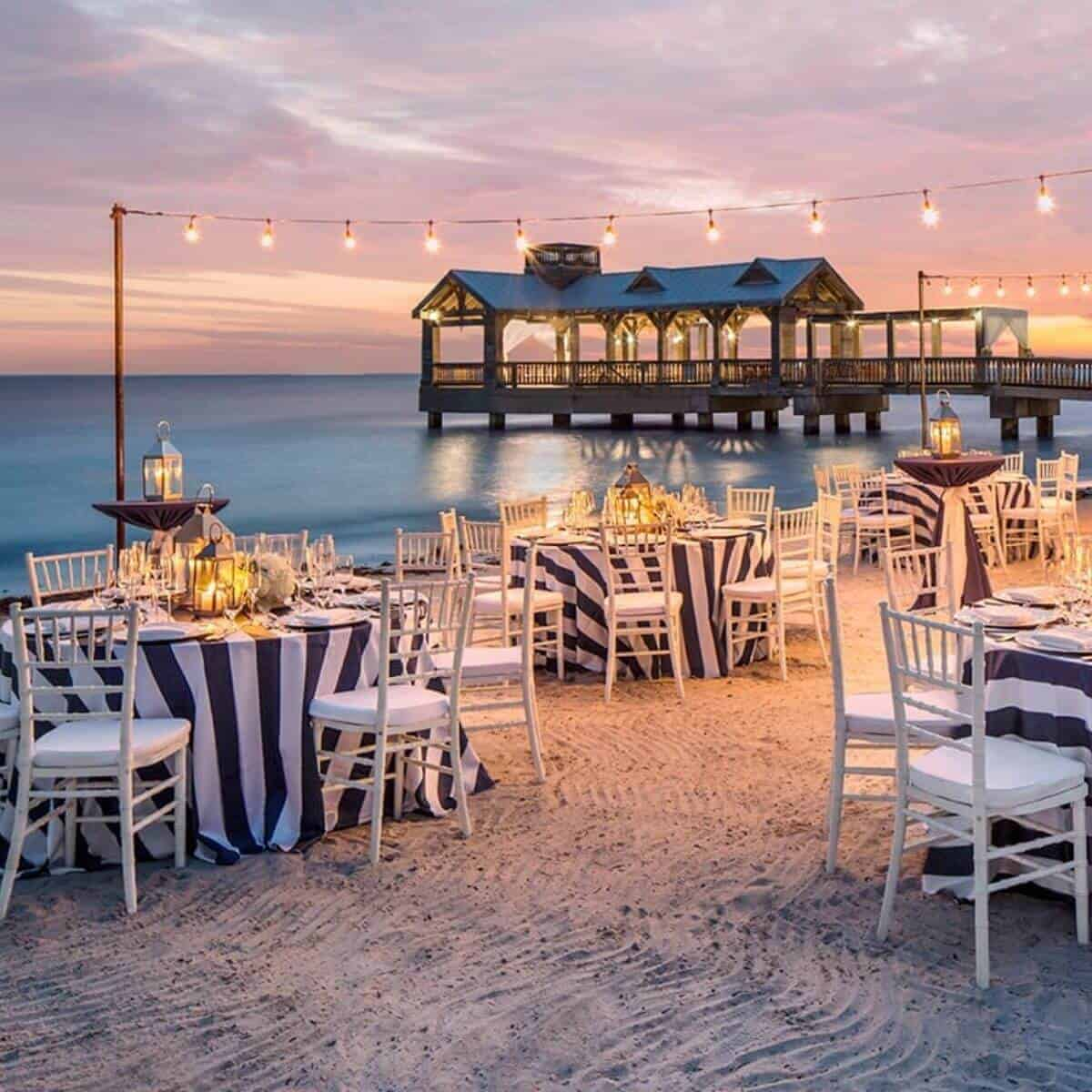 Dining tables and chairs on the beach at The Reach Key West.
