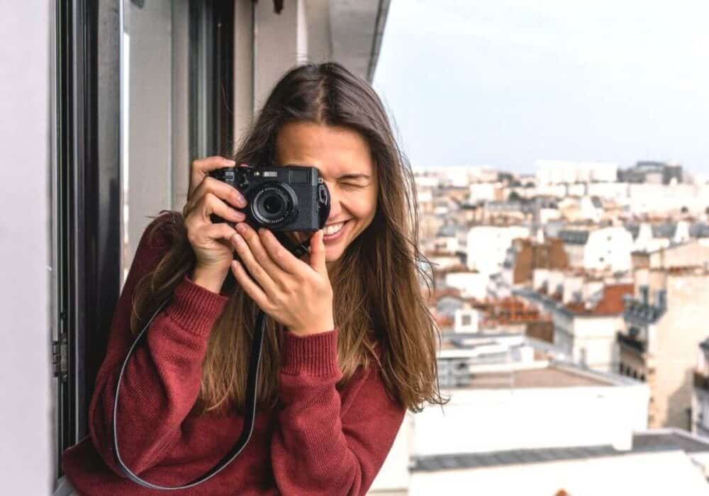 Photographer leaning out of a window to take a photo.