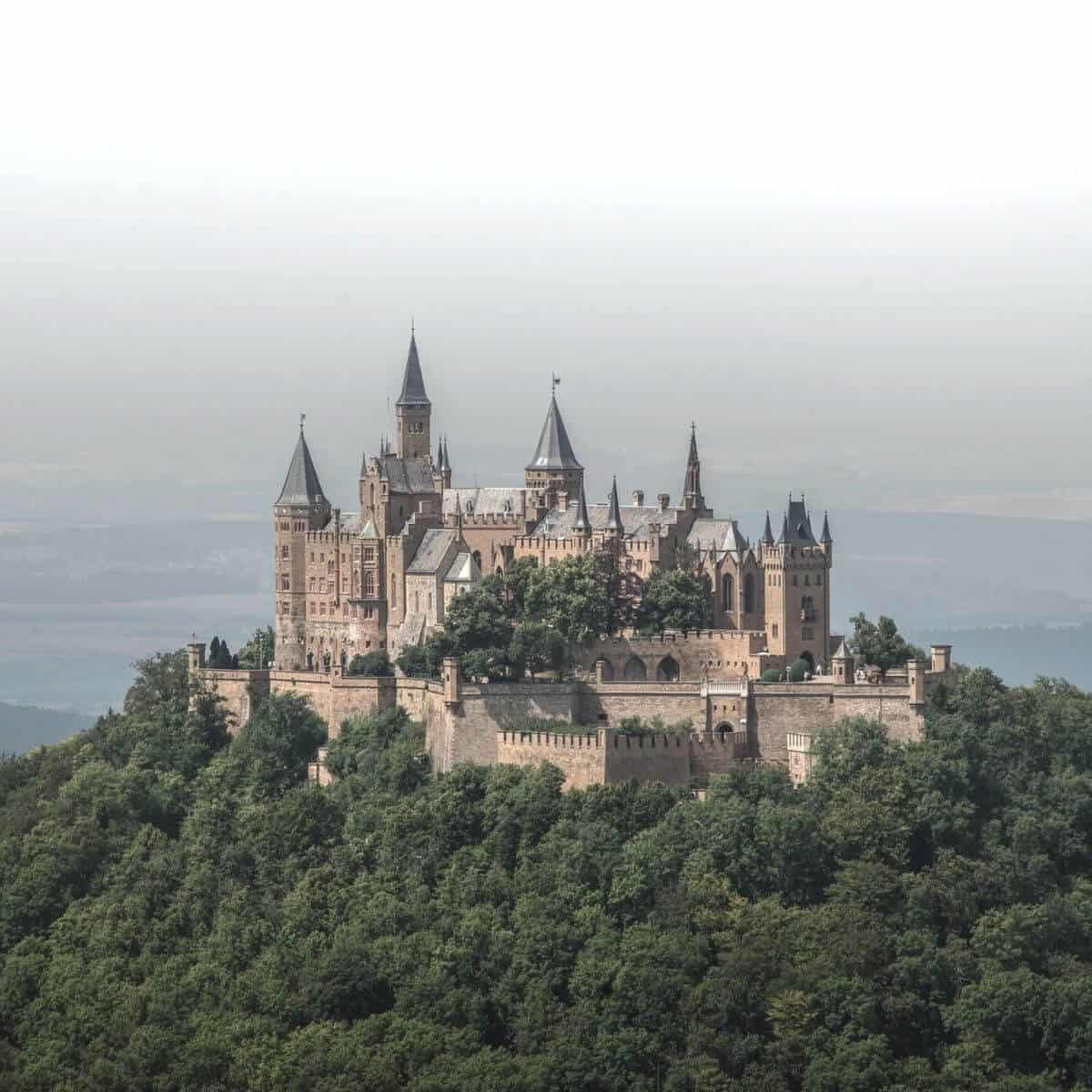 Aerial view of Hohenzollern Castle with fog behind it.