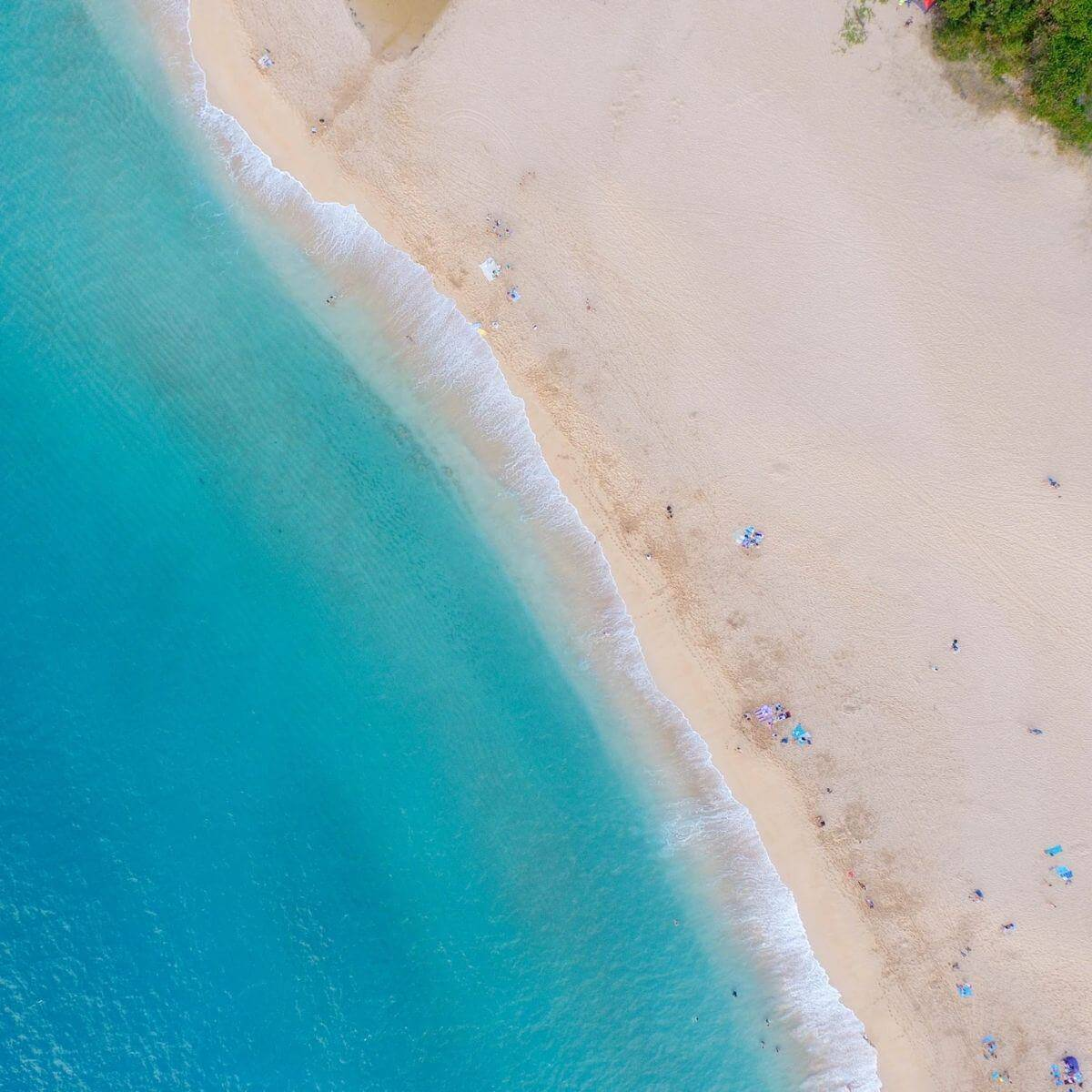 Aerial view of Lanikai Beach with white sand and light blue water.