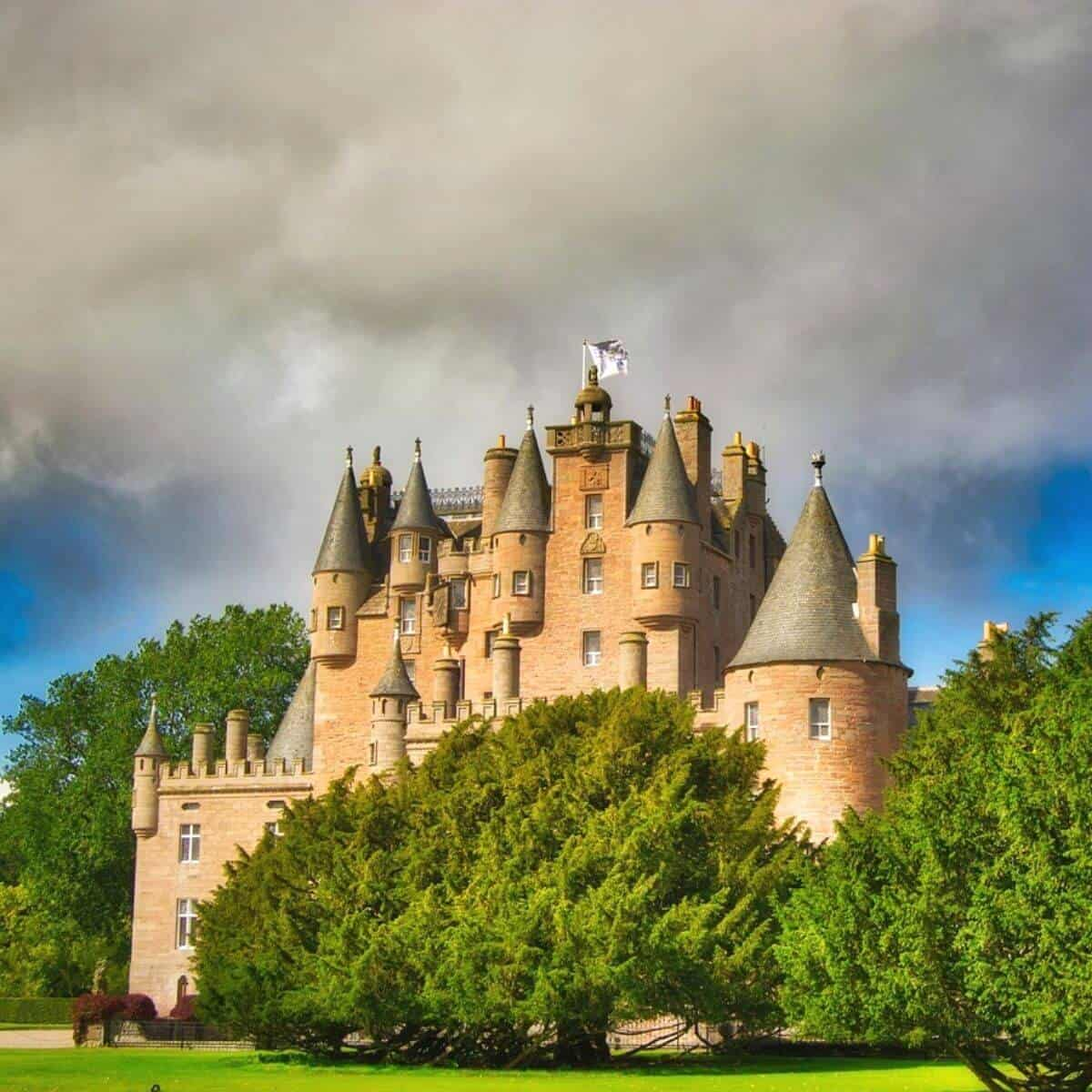 Glamis Castle in Scotland with trees in front and behind it.