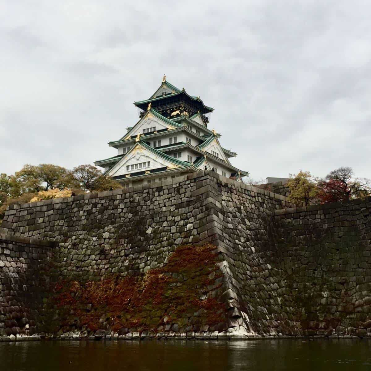 Osaka Castle above a body of water.