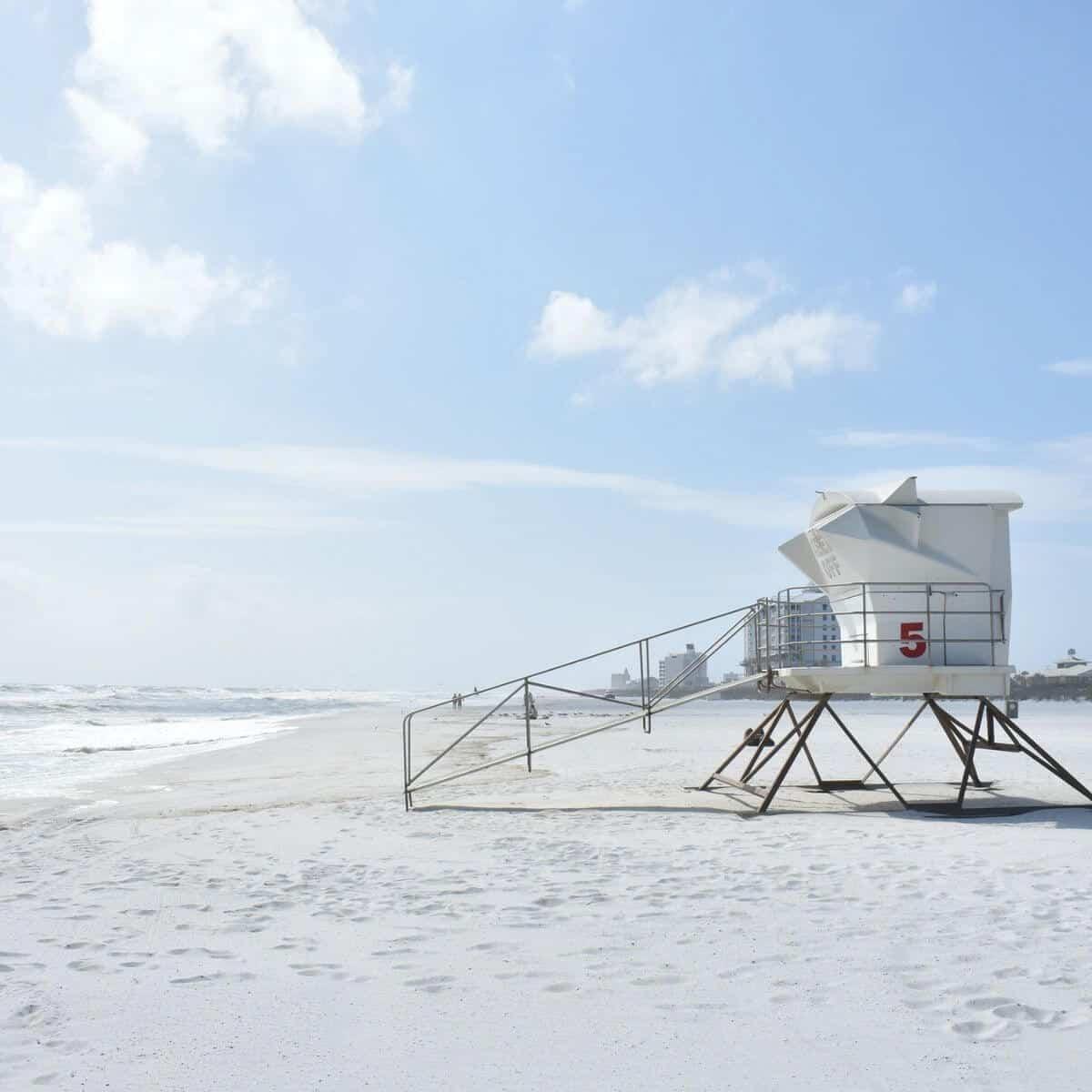 Lifeguard tower on a white sand beach.