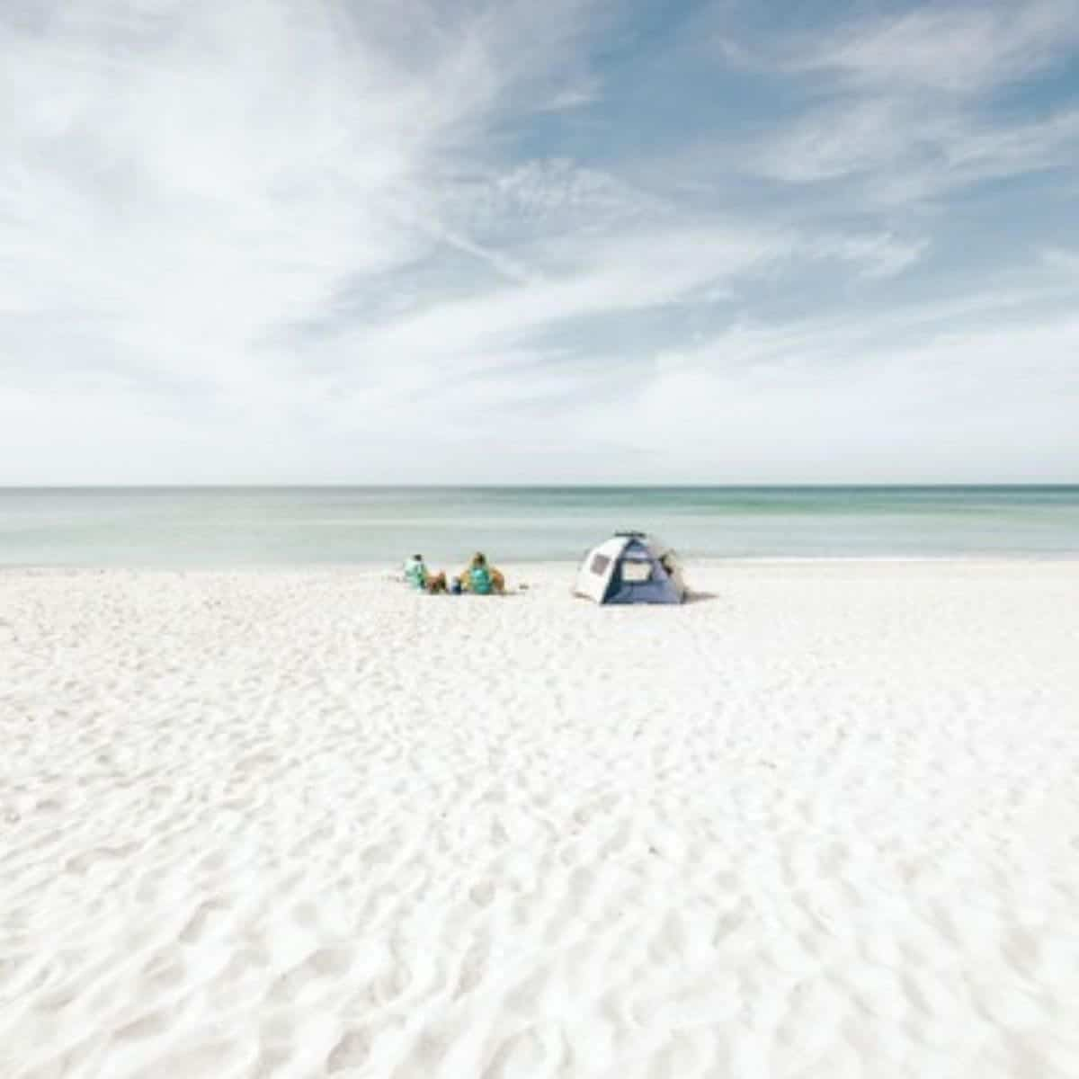 Two people sitting next to a tent on Siesta Key Beach.