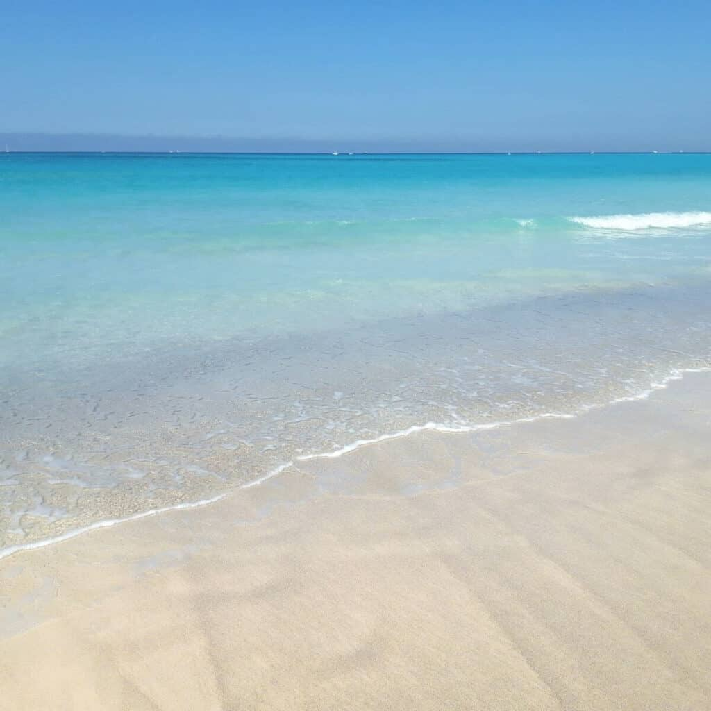 White sand beach with clear water on a sunny day.