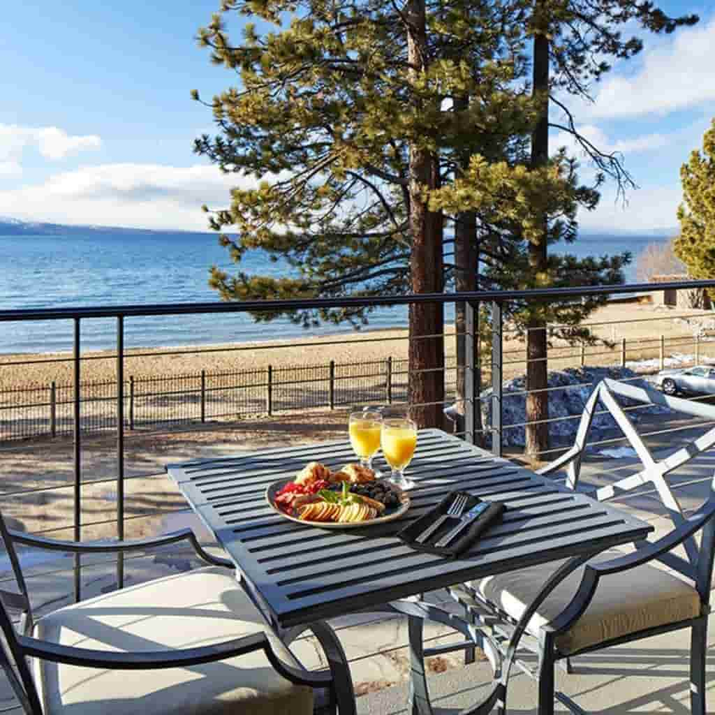 Food and drinks on a patio with a view of trees and Lake Tahoe.