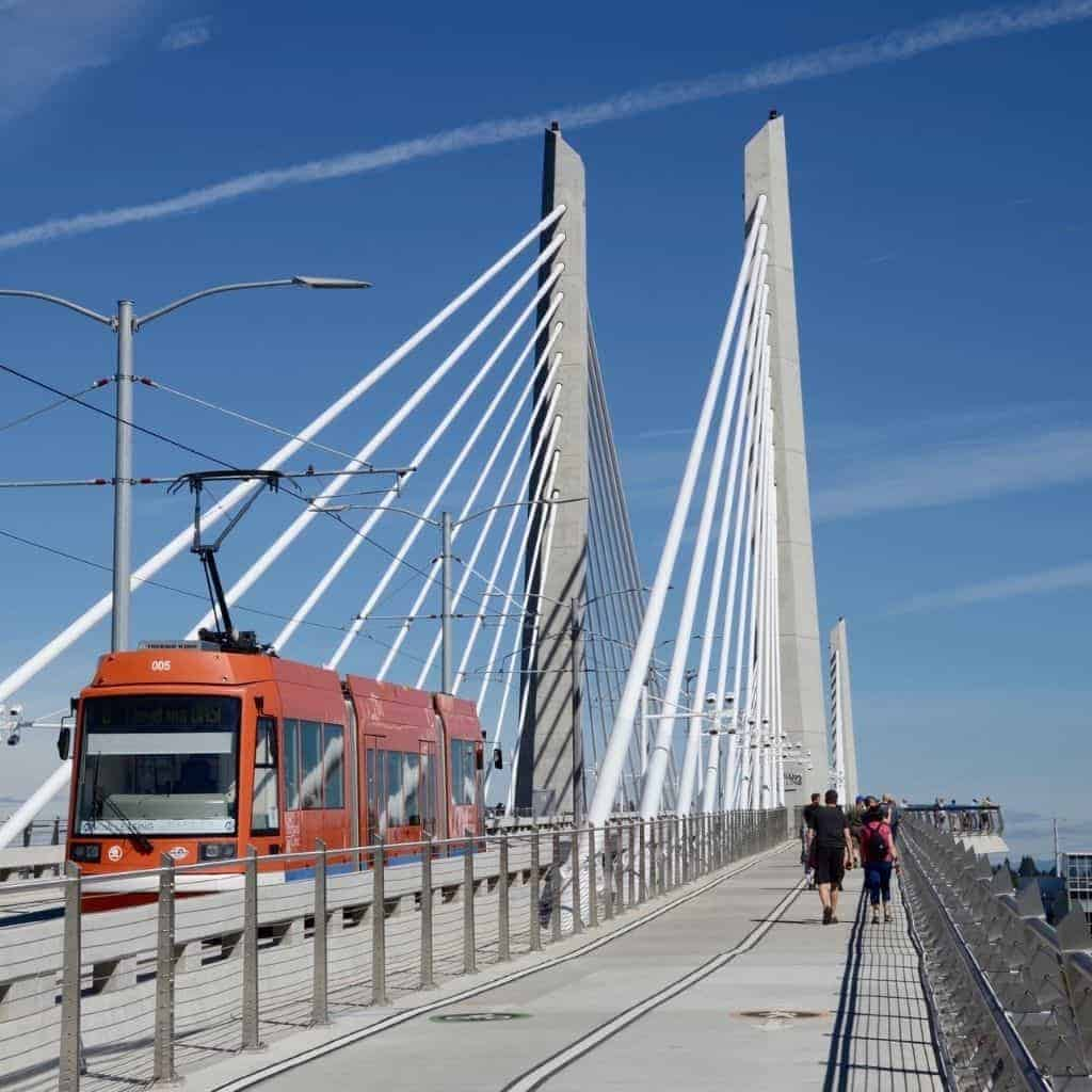 People walking and a light rail on the Tilikum Crossing Bridge.