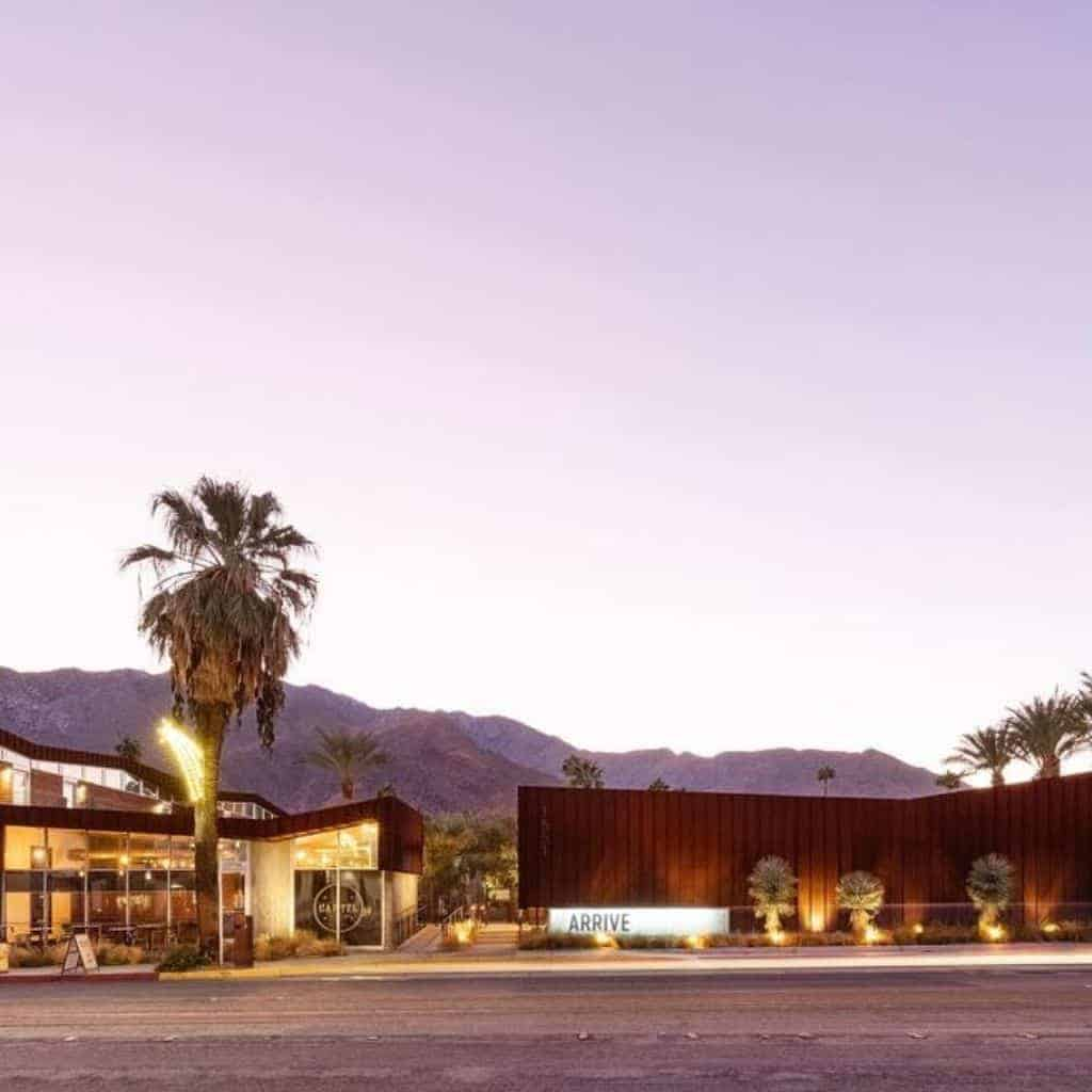Exterior of ARRIVE hotel in Palm Springs with mountains in the background.