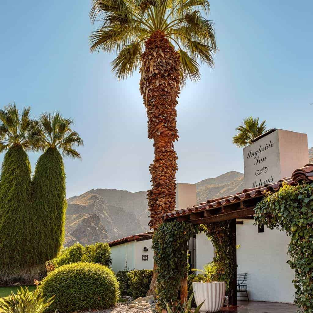 Palm trees, mountains, and exterior of Ingleside Inn.