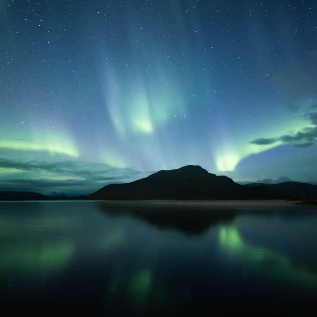View of northern lights and mountains from a lake.