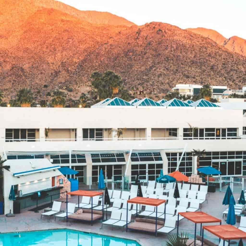 Pool and exterior of Hotel Zoso with mountains in the background.