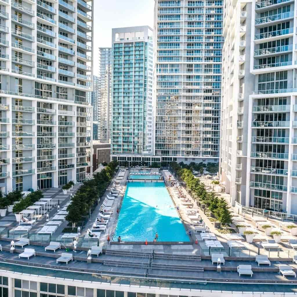 Pool at W Miami surrounded by buildings.
