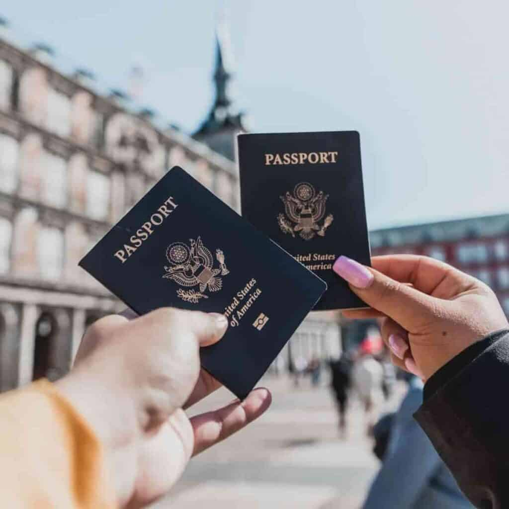 Selective focus on two hands holding passports.